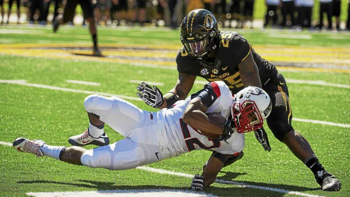 UConn running back Arkeel Newsome, bottom, is tackled by Missouri linebacker Donavin Newsom on Sept. 19.