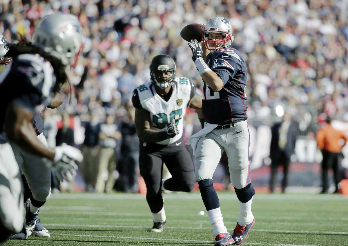 Patriots quarterback Tom Brady (12) throws a touchdown pass to wide receiver Keshawn Martin, foreground, in the second half Sunday.