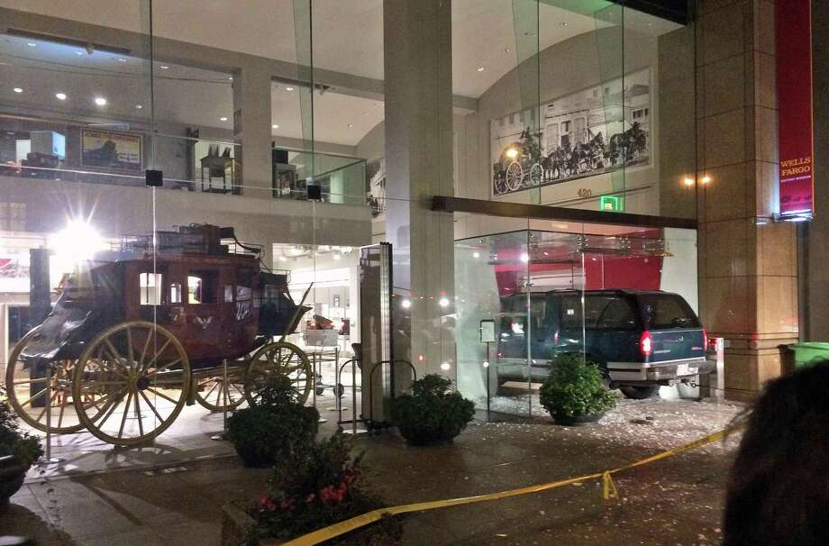 A vehicle is seen smashed into the window of the Wells Fargo History Museum in downtown San Francisco, Tuesday, Jan. 27, 2015. Thieves in the SUV smashed through the glass doors of the museum and made off with gold nuggets on display. (AP Photo/Kristin Bender) Photo: AP / AP