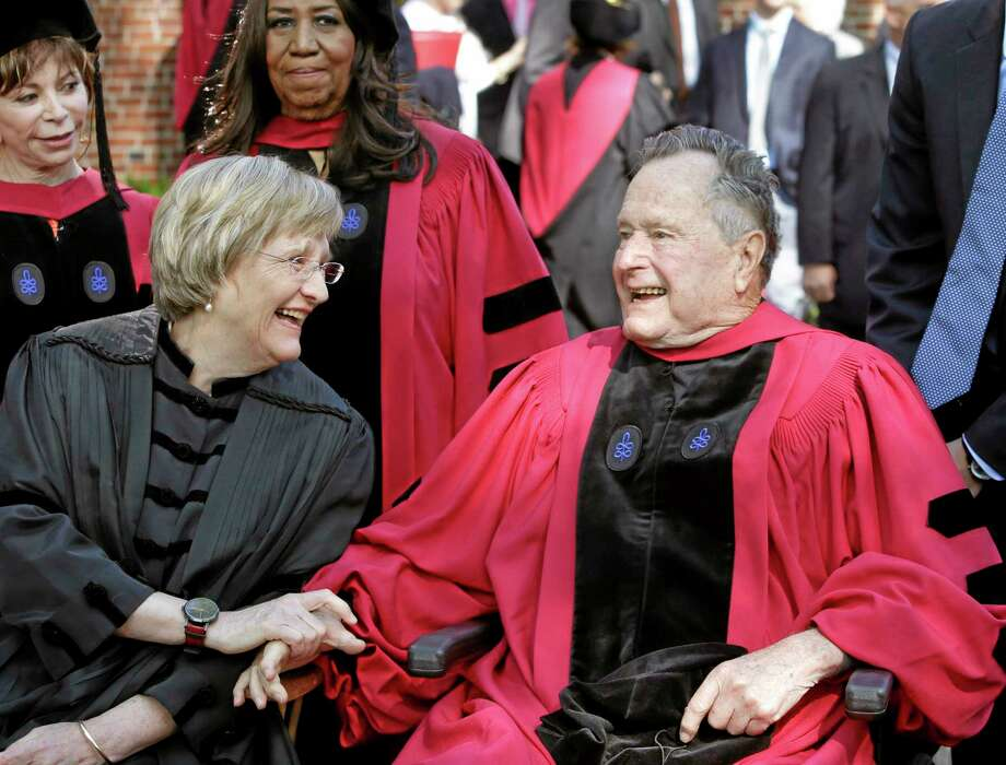 Harvard University President Drew Faust, left, speaks with former President George H. W. Bush, right, before Harvard commencement ceremonies, Thursday, May 29, 2014, in Cambridge, Mass. Bush was presented with with an honorary doctor of laws degree during the ceremonies. Chilean author Isabel Allende, top left, and singer Aretha Franklin, behind center left, look on.  (AP Photo/Steven Senne) Photo: AP / AP
