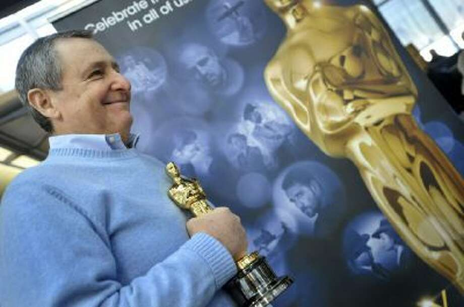 """Tom Sherak waits with an """"Oscar"""" before boarding """"Oscar One"""" heading to Los Angeles for the Academy Awards ceremony, at O'Hare International Airport in Chicago Thursday, Feb. 9, 2012."""