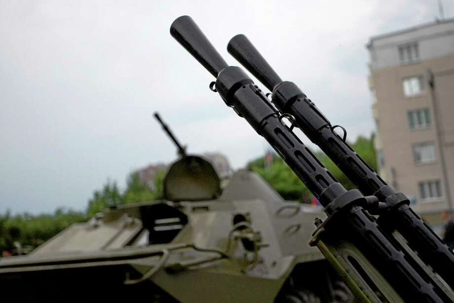 Barrels of an anti-aircraft gun and an APC are seen outside the administration building in Donetsk, Ukraine, on Thursday, May 29, 2014.  Pro-Russian militia in eastern Ukraine shot down a government military helicopter Thursday amid heavy fighting around Slovyansk, killing 14 soldiers including a general. (AP Photo/Ivan Sekretarev) Photo: AP / AP