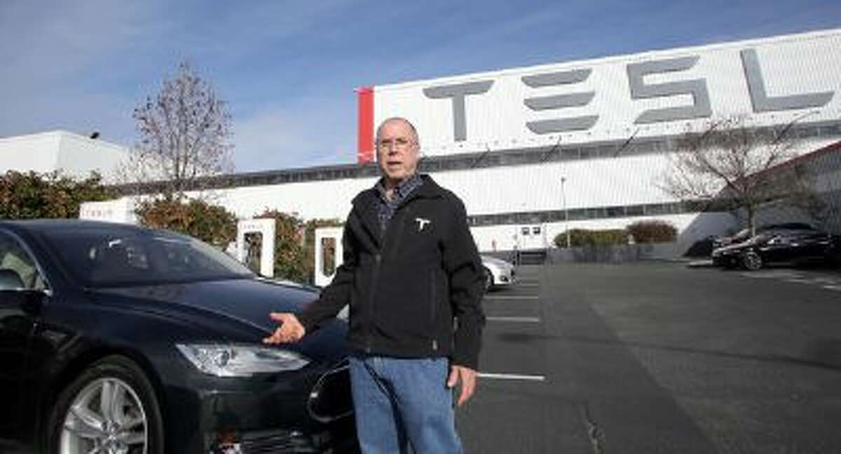John Glenney, 62, of Lexington, Kentucky, talks about his cross country trip in his Tesla Model S sedan, using only the company's Supercharging stations, while charging the car at the Tesla headquarters in Fremont, Calif. on Monday, Jan. 27, 2014.
