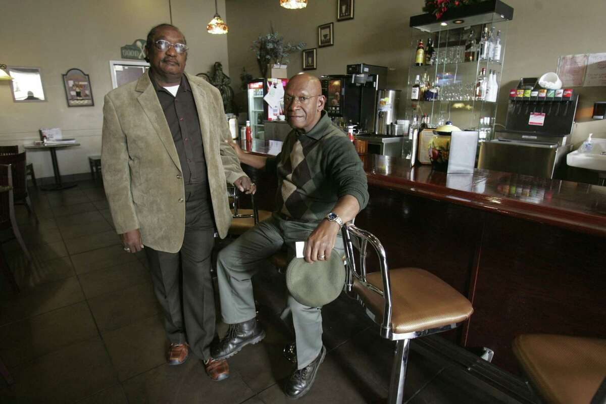 """FILE - In this March 5, 2009, file photo, the Rev. W. T. """"Dub"""" Massey, right, and Willie McLeod, left, pose at the counter where they were among the """"Friendship Nine"""" who were jailed during 1960s civil rights """"sit-ins"""" at what is now called the Old Town Bistro in Rock Hill, S.C. A prosecutor on Wednesday, Jan. 28, 2015, is expected to ask a judge to vacate the arrests and convictions of the eight Friendship Junior College students and a civil rights organizer. (AP Photo/Mary Ann Chastain, File)"""