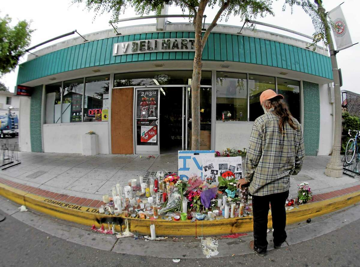 A passerby pays his respects at a makeshift memorial in front of the IV Deli Mart, Sunday, May 25, 2014, the scene of a drive-by shooting Friday in the Isla Vista area near Goleta, Calif. Calif. Sheriff's officials said Elliot Rodger, 22, went on a rampage near the University of California, Santa Barbara, stabbing three people to death at his apartment before shooting and killing three more in a crime spree through a nearby neighborhood. (AP Photo/Chris Carlson)