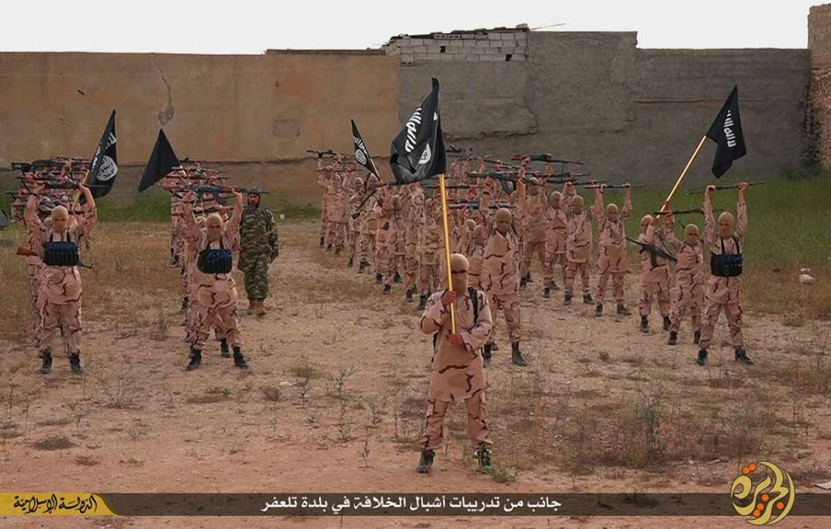 """In this photo released on April 25, 2015 by a militant website, which has been verified and is consistent with other AP reporting, young boys known as the """"lion cubs"""" hold rifles and Islamic State group flags as they exercise at a training camp in Tal Afar, near Mosul, northern Iraq. The Iraqi military has announced an agreement Sunday, Sept. 27, 2015 on """"security and intelligence cooperation"""" with Russia, Iran and Syria to help combat the Islamic State group."""