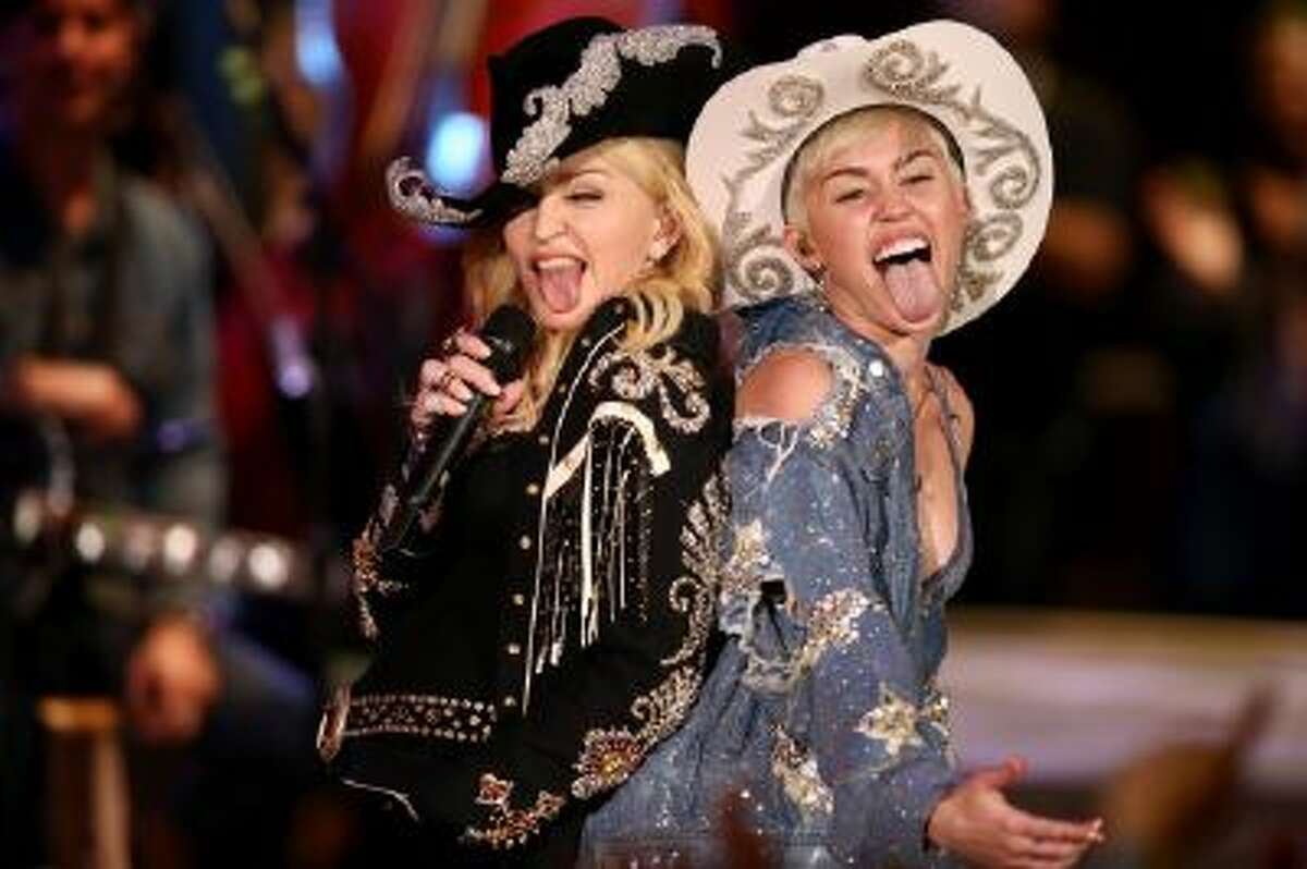 """Miley Cyrus performs with Madonna for MTV Tuesday Jan. 28, 2014. The 21-year-old pop star and the 55-year-old Queen of Pop grinded and grabbed each other as they performed Cyrus' hit """"We Can't Stop"""" and Madonna's 2000 track """"Don't Tell Me"""" Tuesday during a taping in Hollywood. The """"MTV Unplugged"""" special that closes with the duet is set to air Wednesday."""