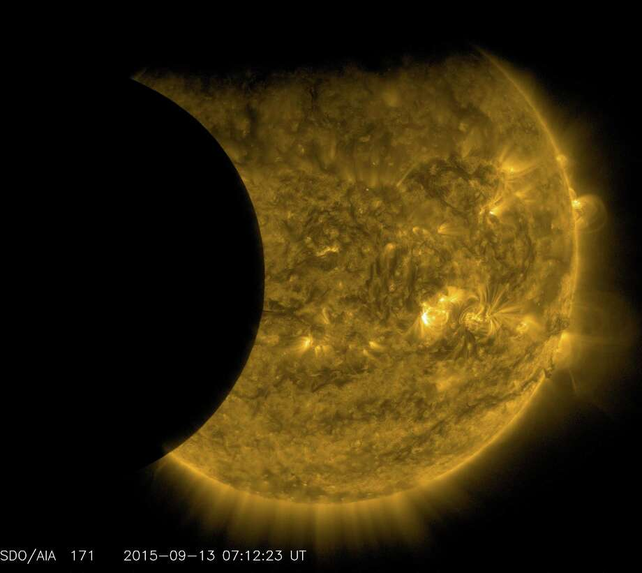 This Sept. 13, 2015 image provided by NASA shows the moon, left, and the Earth, top, transiting the sun together, seen from the Solar Dynamics Observatory. A total lunar eclipse will share the stage with a so-called supermoon Sunday evening, Sept. 27, 2015 as seen from the United States. Photo: NASA/SDO Via AP  / NASA/SDO