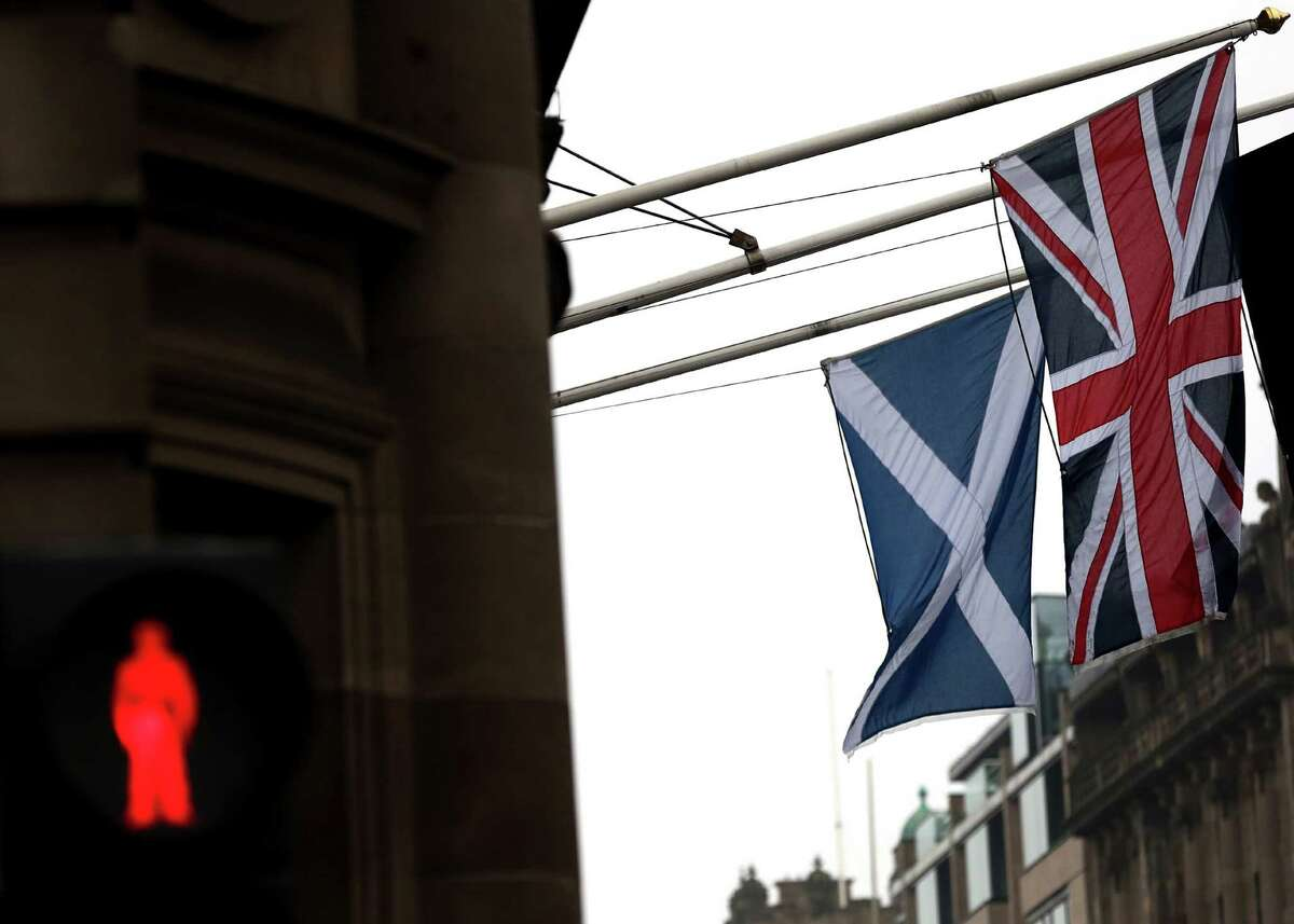 A Saltire and Union Jack flag hang side by side on a building in Edinburgh, Scotland, Sept. 19.