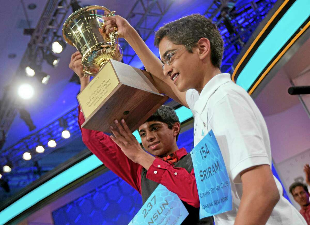 Ansun Sujoe, left, of Fort Worth, Texas, and Sriram Hathwar, right, of Painted Post, N.Y., raise their trophy after being declared co-champions of the Scripps National Spelling Bee, Thursday, May 29, 2014, in Oxon Hill, Md. (AP Photo/Manuel Balce Ceneta)