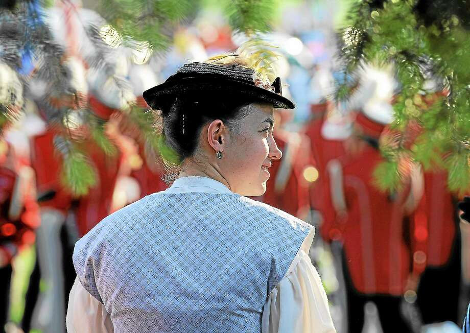 Oliva Delaney of the Comwell Historical Society listens to the Comwell Memorial Day ceremony before the annual parade Thursday evening on the green at Veterans Park in this Photo: Press Archives