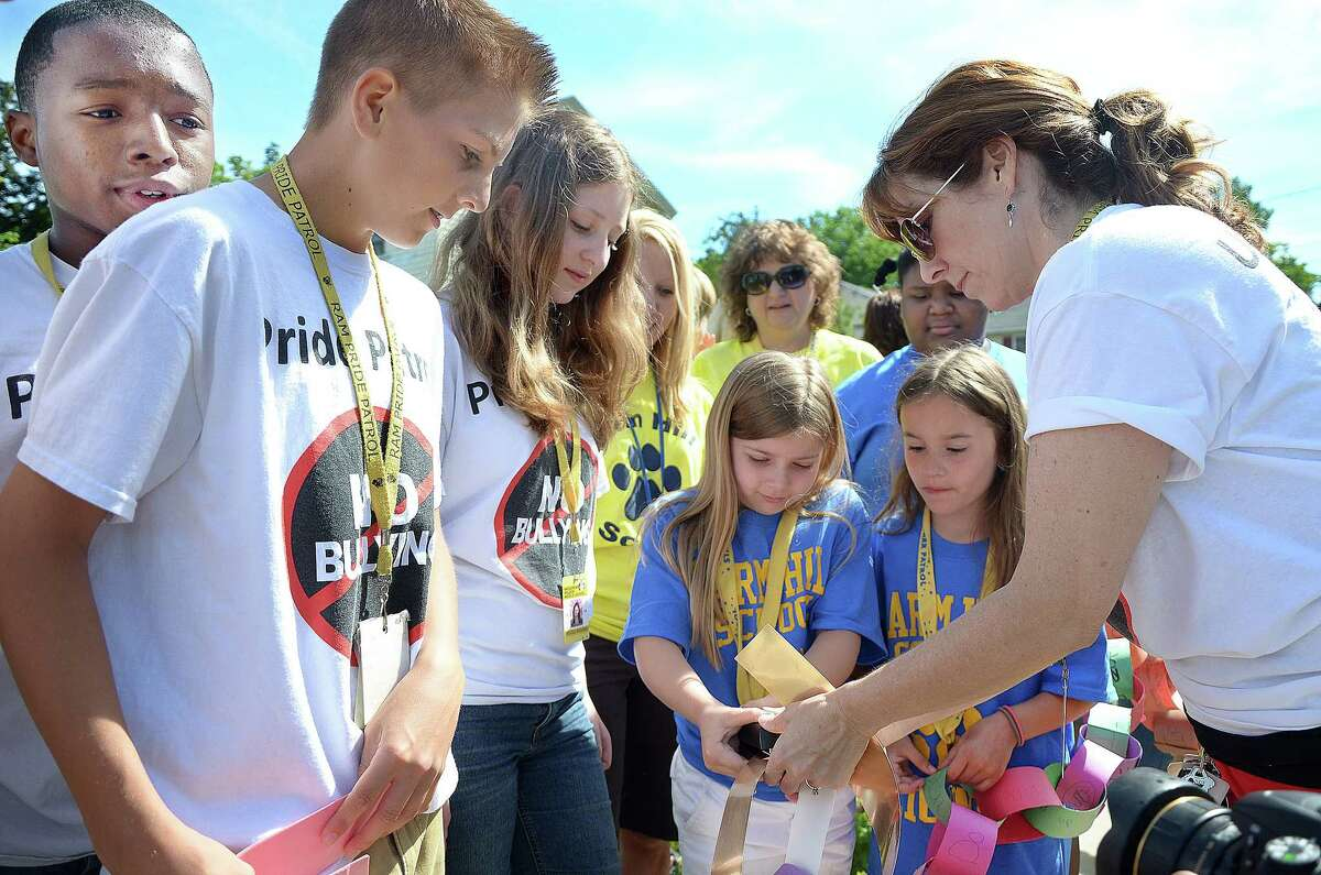 Co-advisor for the Woodrow Wilson Middle School Pride Patrol Monique Nee lends a hand to a Farm Hill Elementary School student who connects paper links from Farm Hill School to those created by the Ram Pride Patrol at the Middletown schools in this 2014 photo.