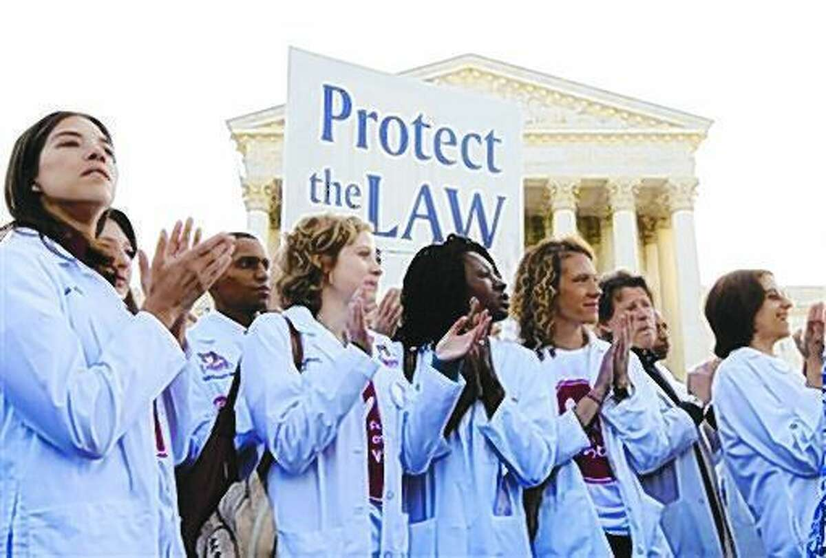 Doctors and medical students gather in front of the Supreme Court in Washington in this March 26, 2012, file photo as the court started three days of arguments on health care.