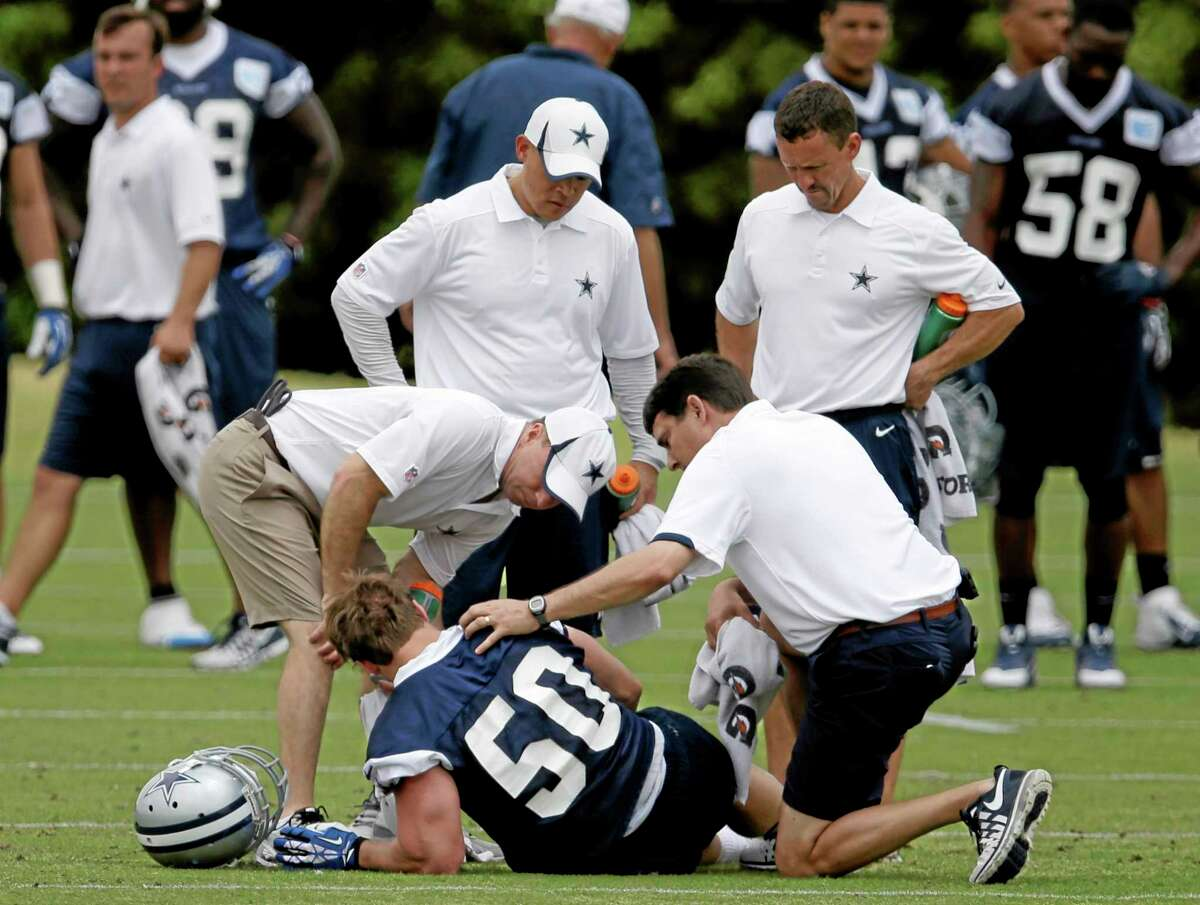 Dallas Cowboys linebacker Sean Lee (50) is attended to by the training staff after suffering an injury during an organized team activity on Tuesday in Irving, Texas.