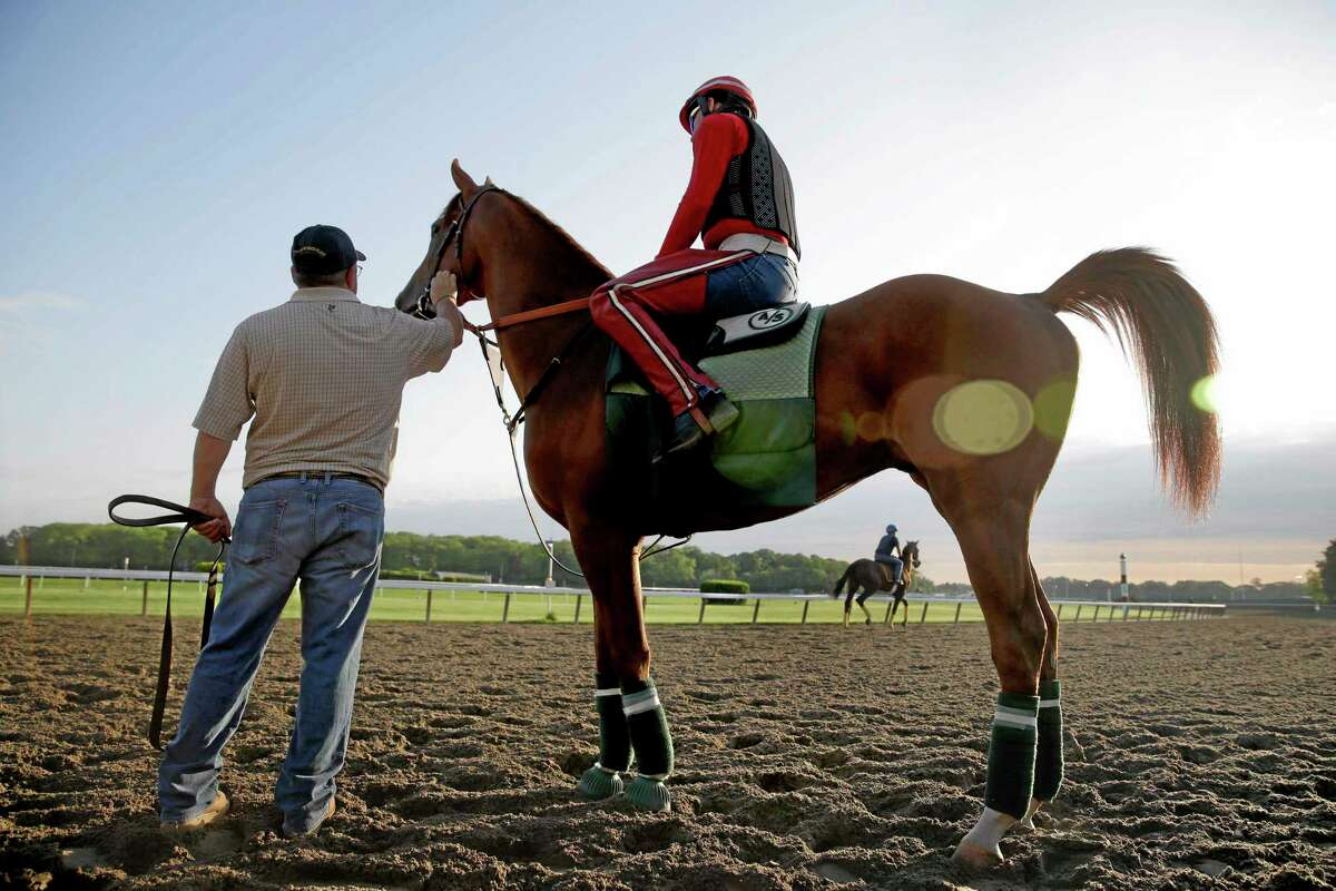 Assistant trainer Alan Sherman, left, leads exercise rider Willie Delgado and California Chrome onto the track at Belmont Park.