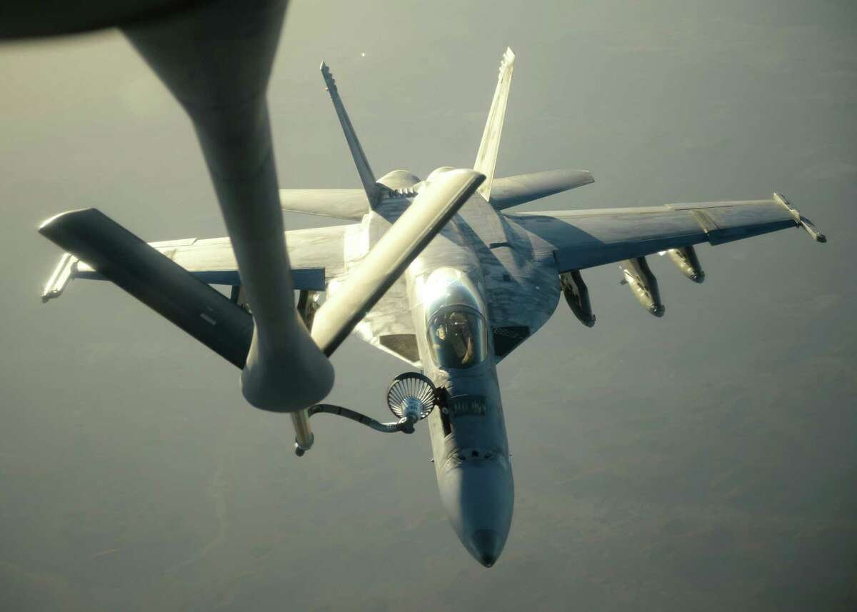 In this Tuesday, Sept. 23, 2014 photo released by the U.S. Air Force, a U.S. Navy F-18E Super Hornet receives fuel from a KC-135 Stratotanker over northern Iraq after conducting airstrikes ias part of U.S. led coalition airstrikes on the Islamic State group and other targets in Syria. U.S.-led airstrikes targeted Syrian oil installations held by the militant Islamic State group overnight and early Thursday, Sept. 25, 2014, killing nearly 20 people as the militants released dozens of detainees in their de facto capital, fearing further raids, activists said. (AP Photo/U.S. Air Force, Staff Sgt. Shawn Nickel)
