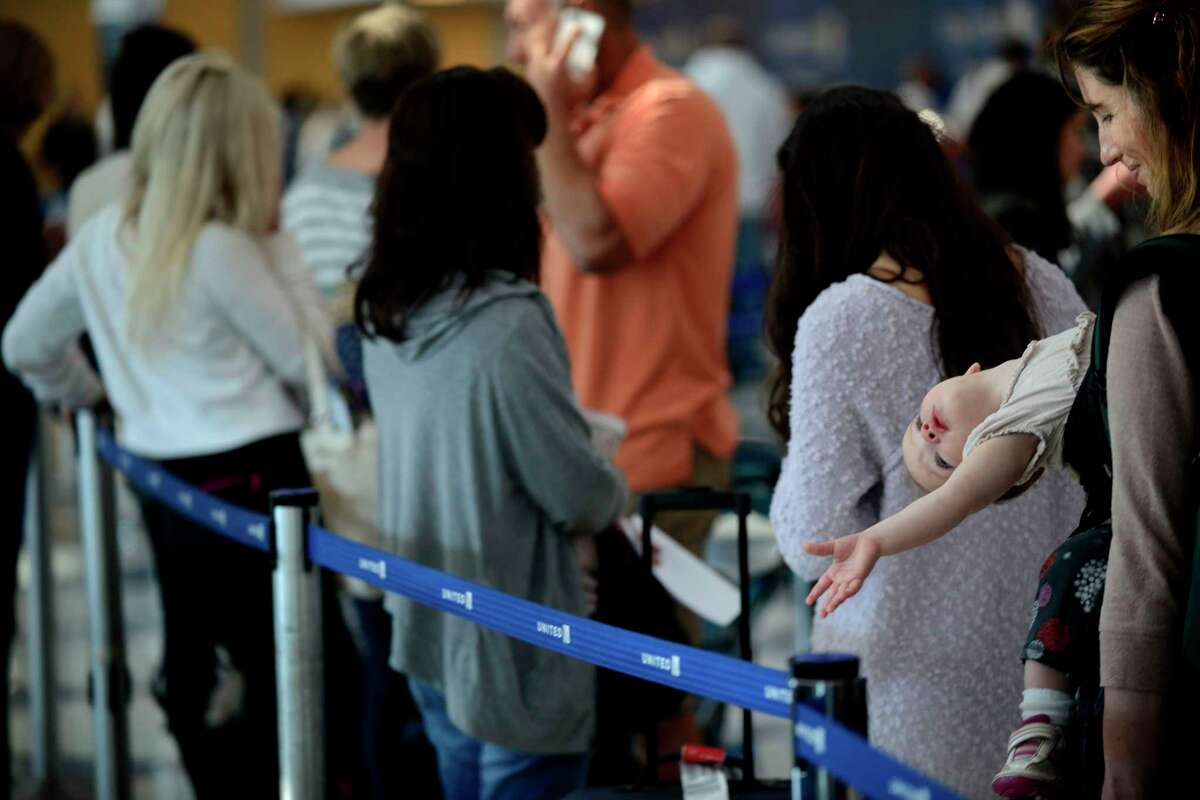 Ann Walden and her 15 month-old daughter Delphine wait in-line after their flight to Baton Rouge was delayed at O'Hare International Airport in Chicago, Friday, Sept. 26, 2014. (AP Photo/Paul Beaty)