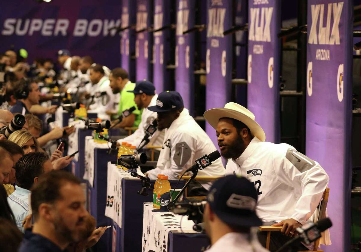 Seattle Seahawks defensive end Michael Bennett and other teammates answer questions during Super Bowl media day on Tuesday in Phoenix.