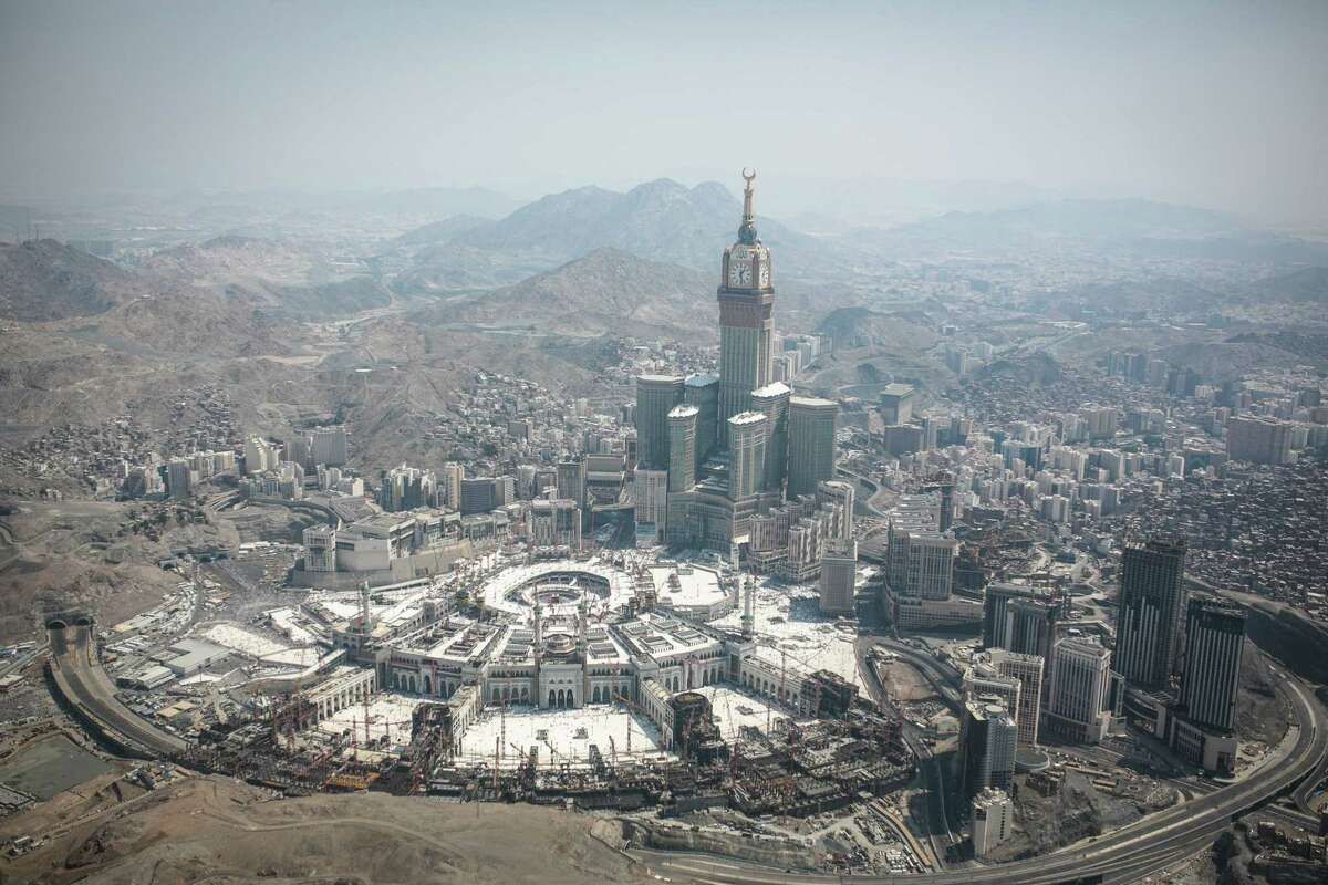 In this aerial photo made from a helicopter, the Abraj Al-Bait Towers with the four-faced clocks stands over the holy Kaaba, as Muslims encircle it inside the Grand Mosque, during the annual pilgrimage known as the hajj, in the Muslim holy city of Mecca, Saudi Arabia, Friday, Sept. 25, 2015.