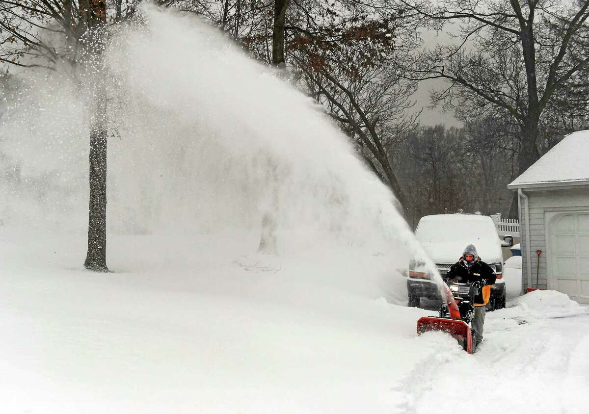(Peter Hvizdak - New Haven Register) Jen Hanrahan uses a snowblower to clear her driveway on Pine Orchard Road in Branford, Conn., at 21F degrees, with gusty winds from the North at 20-mph, which feels like 1F degrees Tuesday, January 27, 2015.