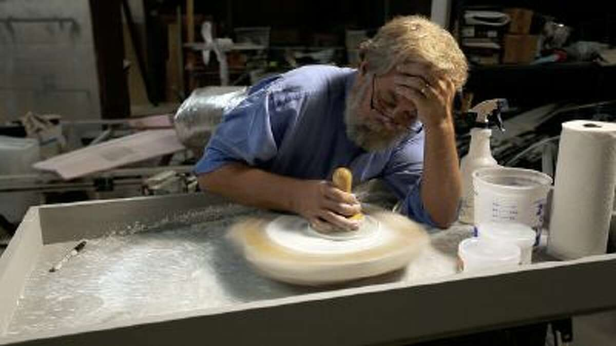 This film image released by Sony Pictures Classics shows Tim Jenison polishing a lens in