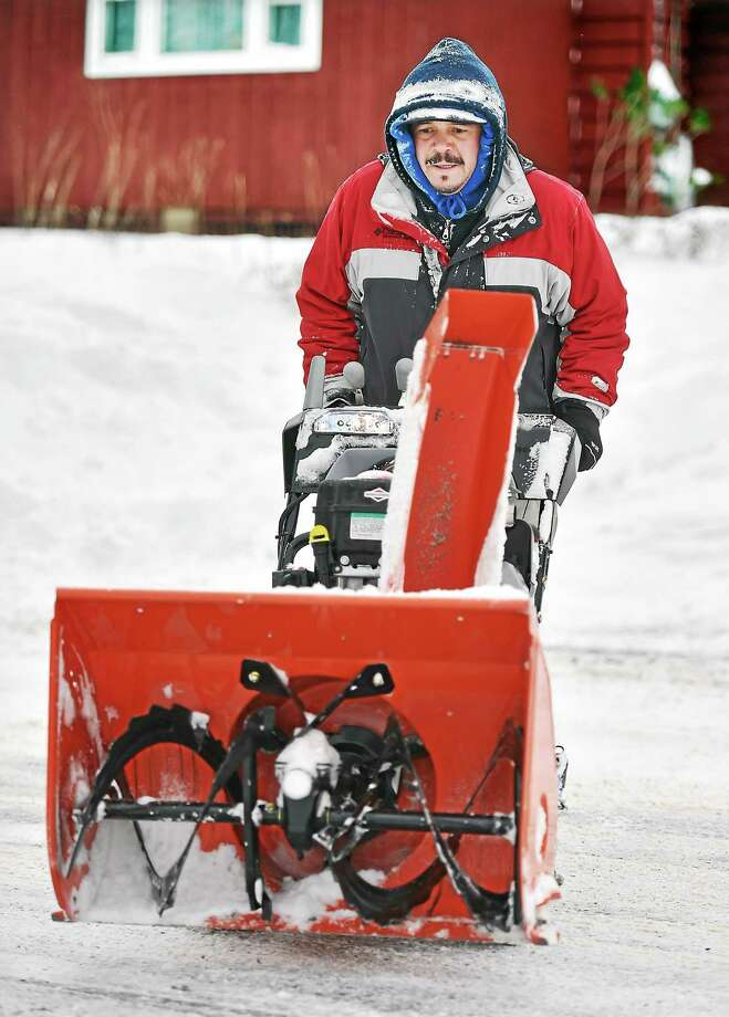 (Catherine Avalone - New Haven Register) Middletown resident Hector Adorno heads back home after clearing snow from a neighbor's driveway on Highland Avenue in Middletown, Tuesday, January 27, 2015 . Photo: Journal Register Co. / New Haven RegisterThe Middletown Press