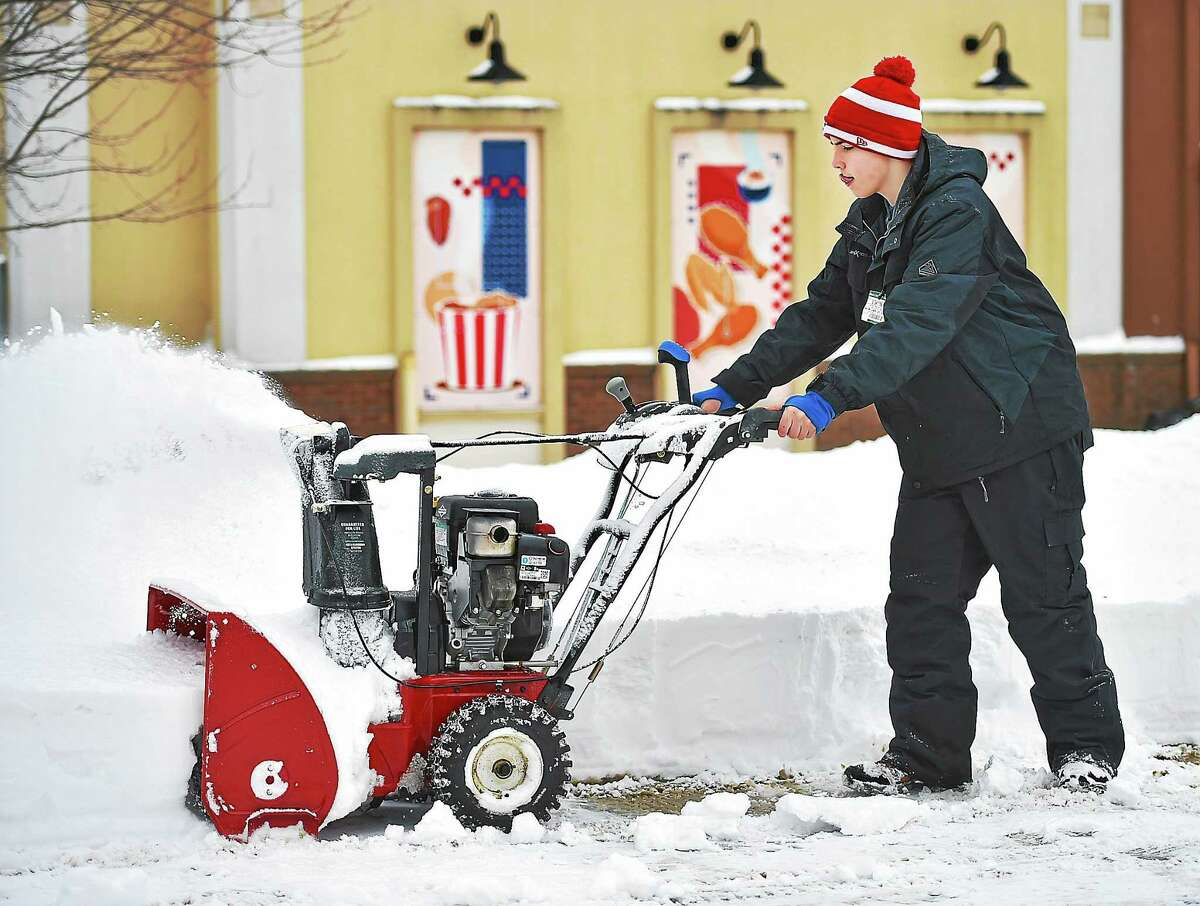 (Catherine Avalone - New Haven Register) Middletown resident Sean Elmeer, 14, a freshman at Xavier High School uses a snow blower to clear snow from the parking lot at Domino's Pizza Tuesday, January 27, 2015. Elmeer's father, Andrew owns the fast food pizza restaurant on South Main Street in Middletown.