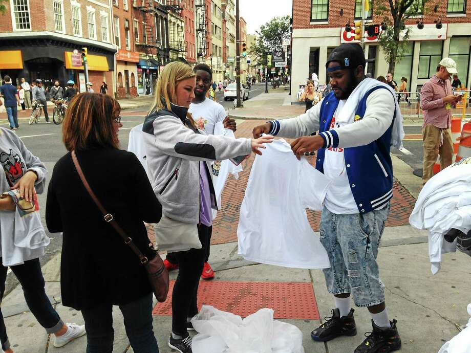 Caitlyn Cummings buys a pope shirt from street merchant Zac Coumbassa near 3rd and Market during Pope Francis' visit to Philadelphia. Photo: Jenn Lucas — Digital First Media