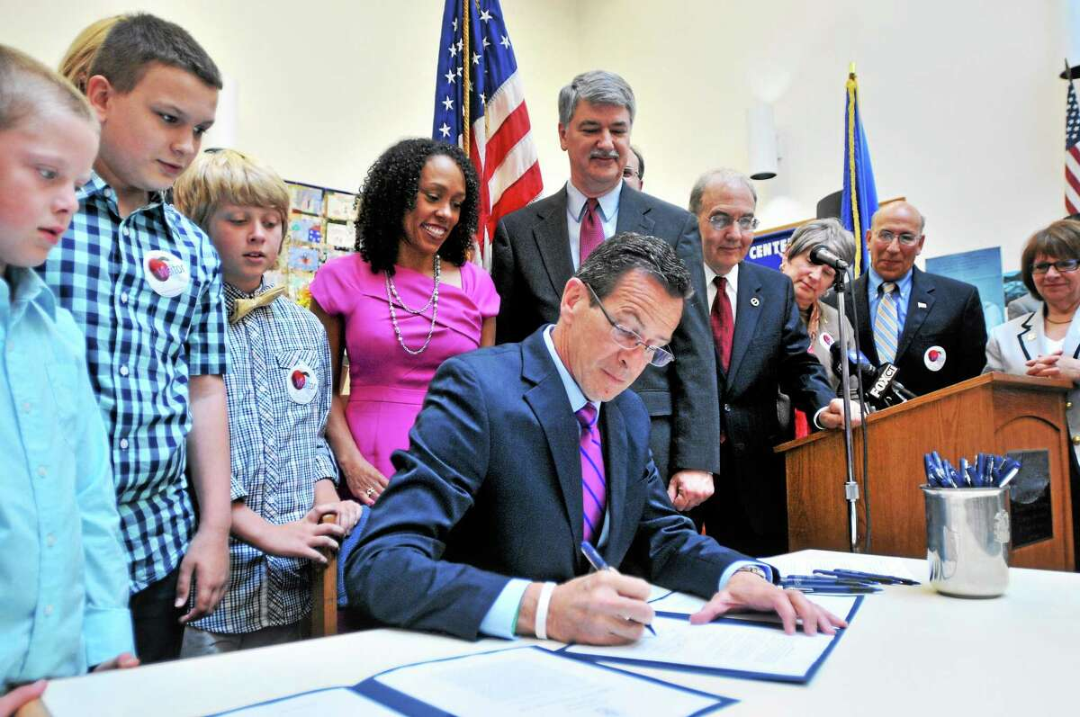 Gov. Dannel P. Malloy, center, signs Public Acts No. 14-39 and 14-41 expanding pre-kindergarten for 3- and 4-year-olds and establishing the Office of Early Childhood at the Helen Street School in Hamden Wednesday.