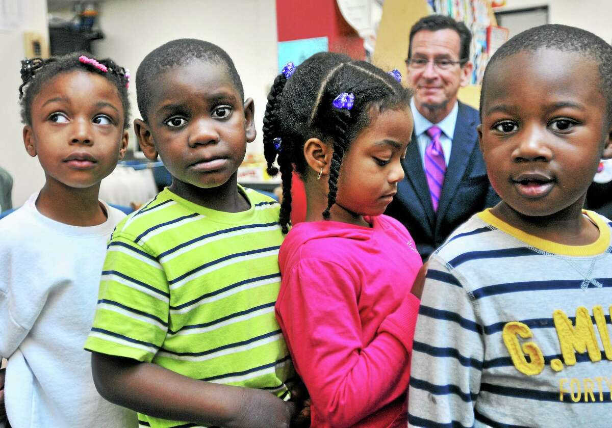 Gov. Dannel P. Malloy, right, watches pre-kindergarten students file in for a song at the Helen Street School in Hamden Wednesday.
