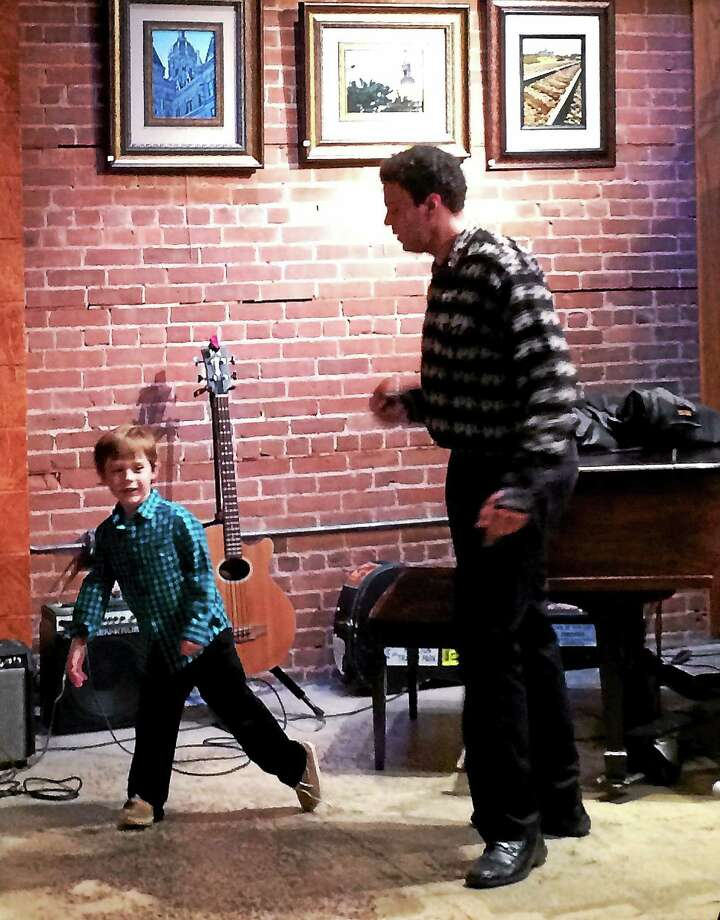 Basil Ali performs with Jax, 5, a young open mic fan at the Buttonwood Tree on Main Street in Middletown. Photo: Courtesy Buttonwood Tree