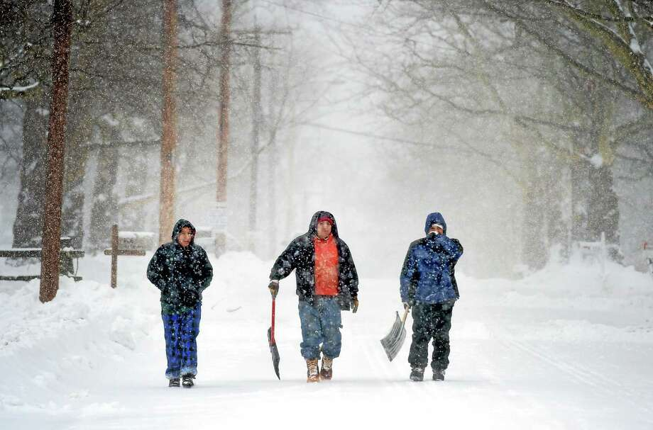 (Arnold Gold-New Haven Register)  A trio of shovelers makes their way down Sky Top Drive in Fairfield looking for business on 1/27/2015. Photo: Journal Register Co.