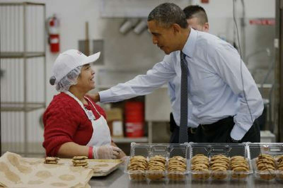 President Barack Obama greets an employee in the bakery at a Costco store in Lanham, Md., Wednesday