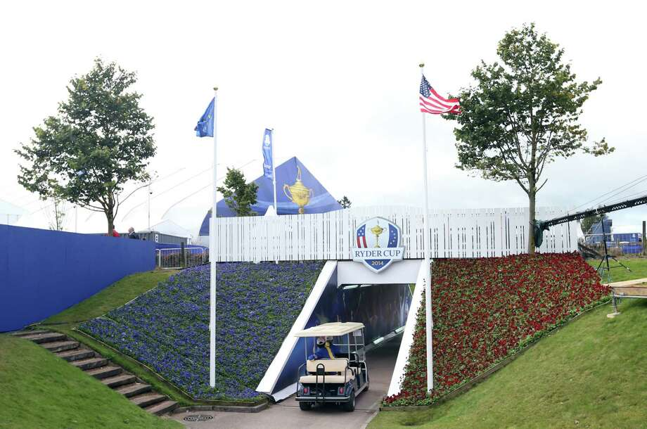 A golf buggy drives through a walkway decorated with former winning captains and players of the Ryder Cup Thursday at Gleneagles, Scotland. Photo: Scott Heppell — The Associated Press  / AP