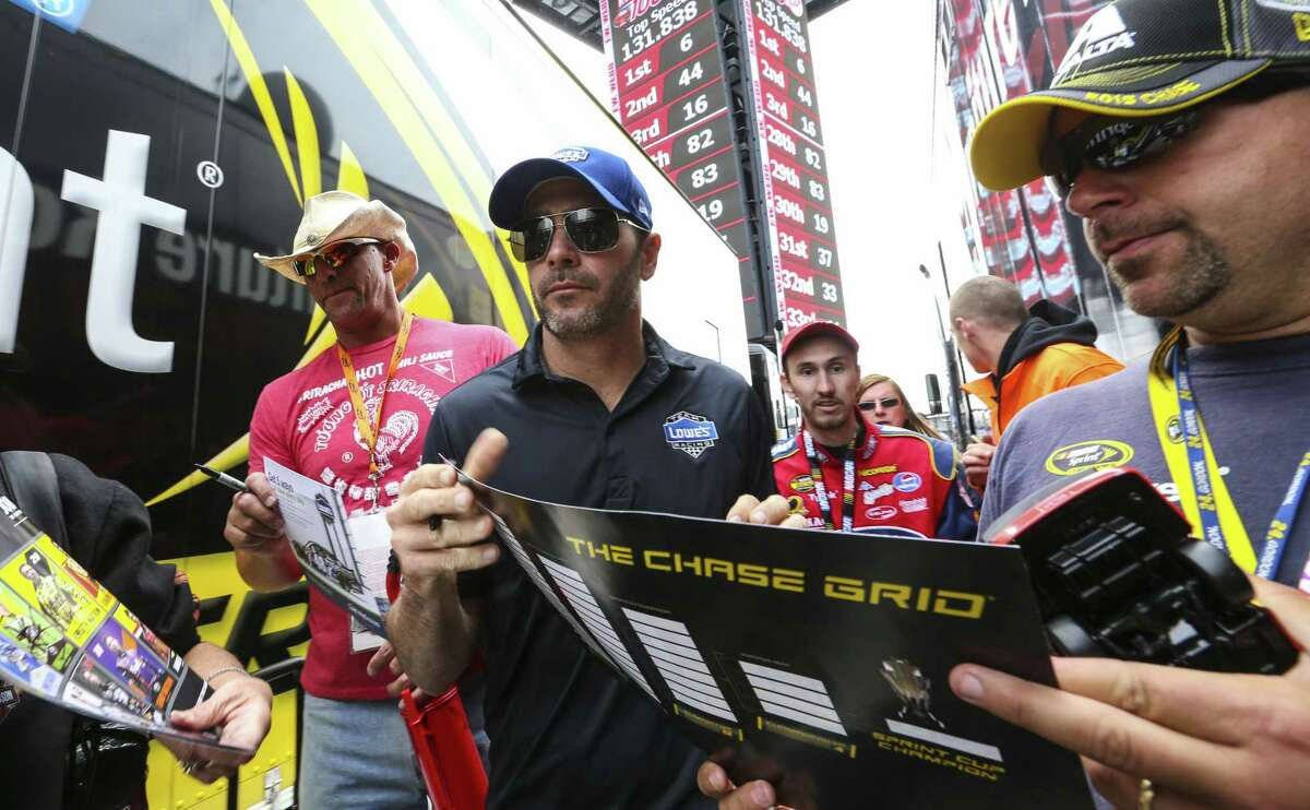 Driver Jimmie Johnson, center, signs autographs for fans before practice for Sunday's NASCAR Sprint Cup race at New Hampshire Motor Speedway in Loudon, N.H.