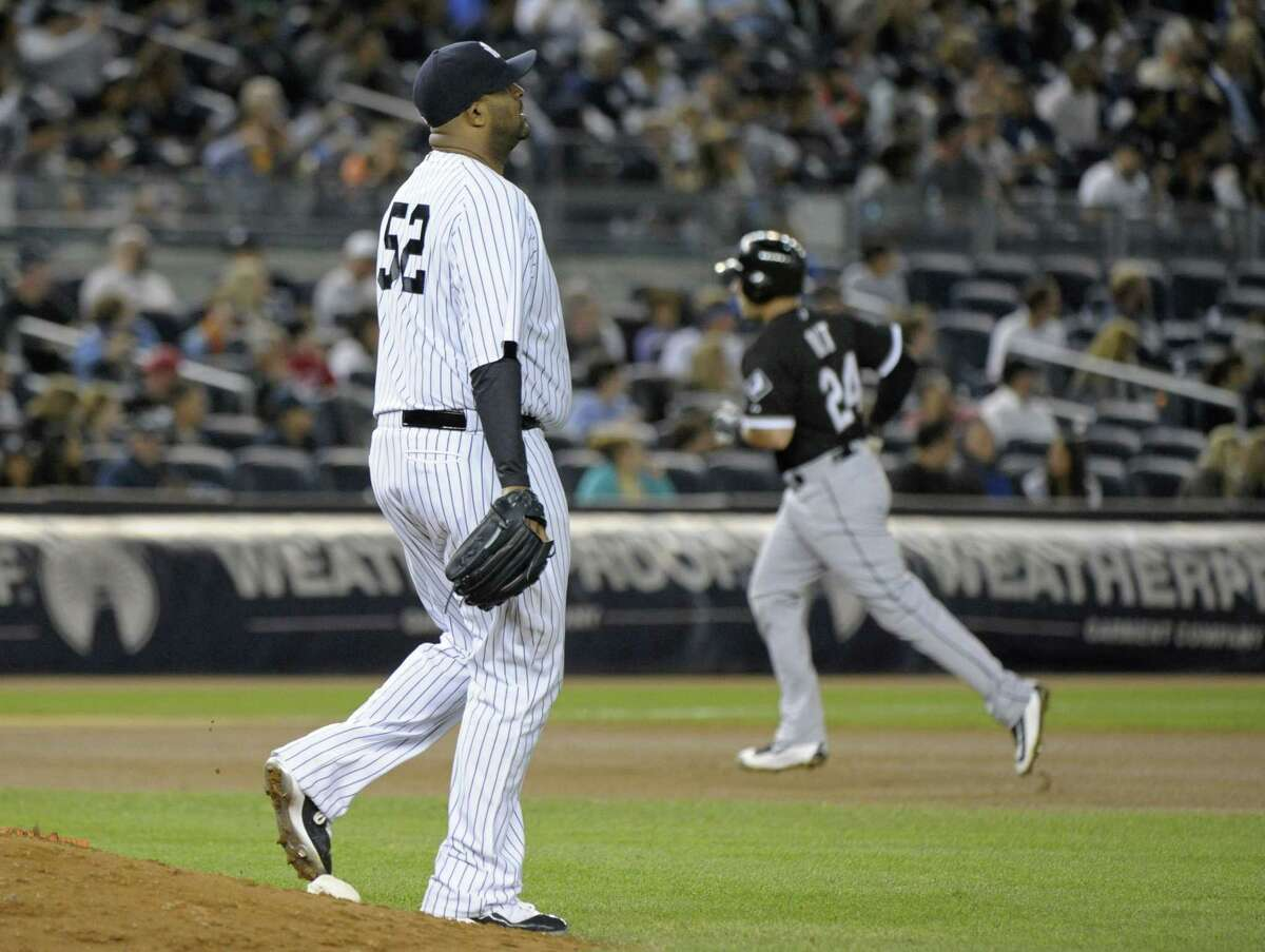 Yankees pitcher CC Sabathia reacts as the White Sox's Mike Olt, right, rounds the bases with a home run during the seventh inning Friday.