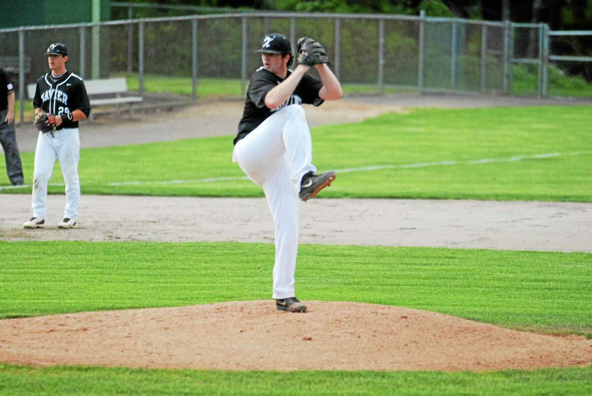 Xavier senior Sean Carroll delivers a pitch against Cheshire on Tuesday at Palmer Field. Carroll was the winning pitcher.