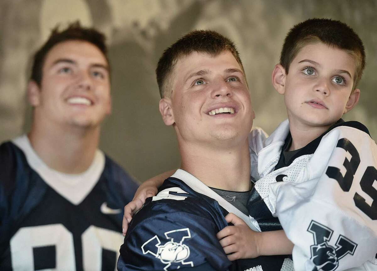 """Yale sophomore tight end Jackson Stallings holds 6-year-old teammate Dante Chiappetta of North Haven while watching a video during """"Yale Bulldogs Draft Day"""" this past September."""