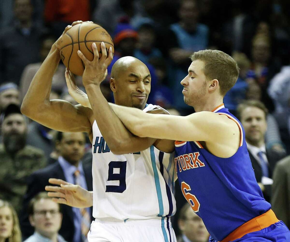 New York Knicks forward Travis Wear, right, fouls Hornets forward Gerald Henderson during Saturday's game in Charlotte, N.C.