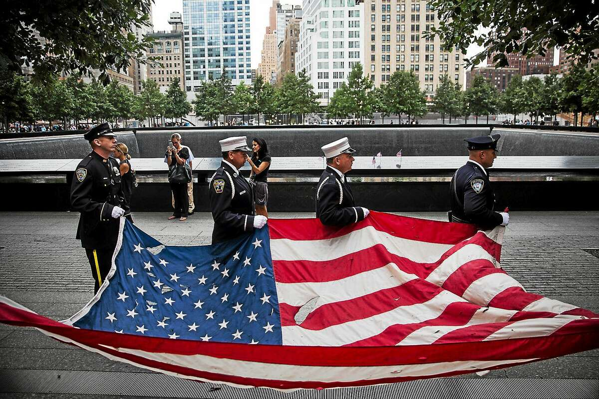 Members of the New York Police Department, Fire Department of New York and Port Authority of New York and New Jersey Police Department carry an American flag at the beginning of the memorial observances on the 13th anniversary of the Sept. 11 terror attacks on the World Trade Center in New York, Thursday, Sept. 11, 2014.
