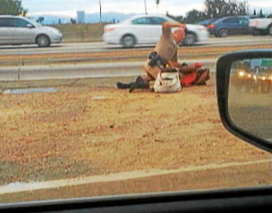 In this July 1, 2014 file image made from video provided by motorist David Diaz, a California Highway Patrol officer straddles a woman while punching her on the shoulder of a Los Angeles freeway. Photo: AP Photo/David Diaz, File  / David Diaz