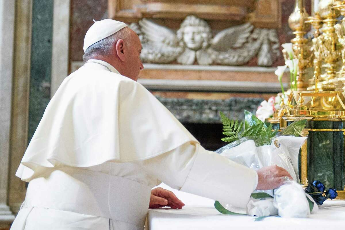 In this photo provided by the Vatican newspaper L'Osservatore Romano, Pope Francis offers flowers in the Saint Mary Major Basilica in Rome to thank the Virgin Mary after his Mideast trip, Tuesday, May 27, 2014. (AP Photo/L'Osservatore Romano, ho)