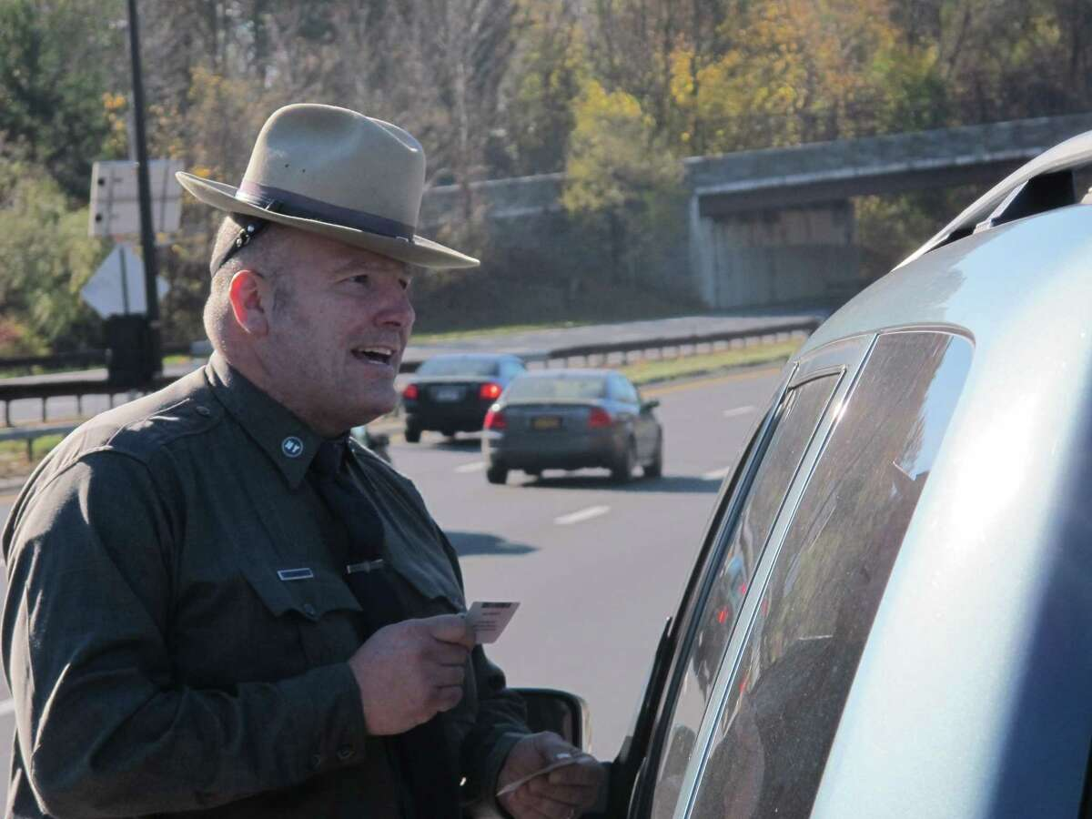 New York State Trooper Clayton Howell checks a driver's license after making a traffic stop for distracted driving in Greenburgh, N.Y., in this 2013 file photo.