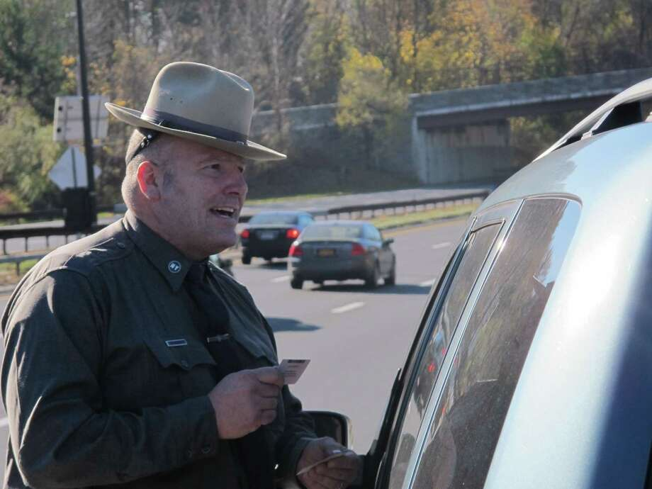 New York State Trooper Clayton Howell checks a driver's license after making a traffic stop for distracted driving in Greenburgh, N.Y., in this 2013 file photo. Photo: AP Photo  / AP