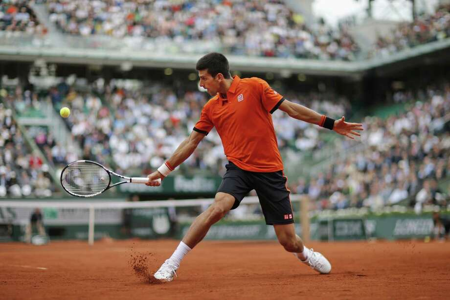 Novak Djokovic returns in his first-round match of the French Open against Jarkko Nieminen on Tuesday in Paris. Photo: Christophe Ena — The Associated Press  / AP