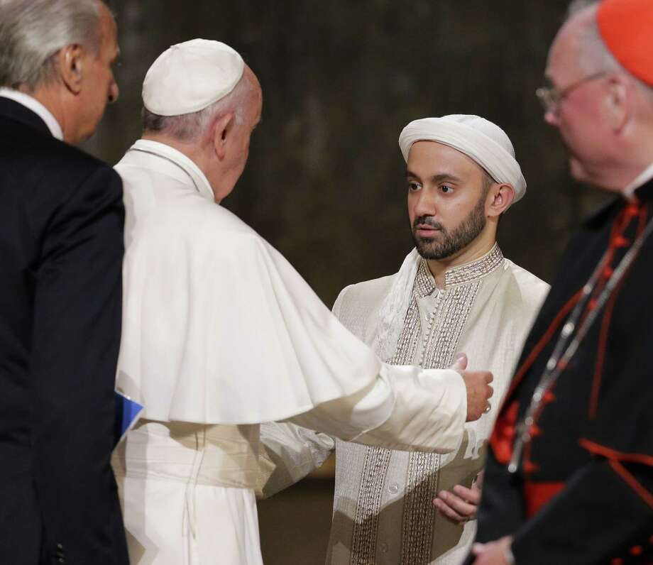 Pope Francis, second left, and Iman Khalid Latif, executive director of the Islamic Center, reach to hug during a multi-religious gathering at the National September 11 Memorial Museum in New York on Friday. Photo: AP Photo  / POOL EPA