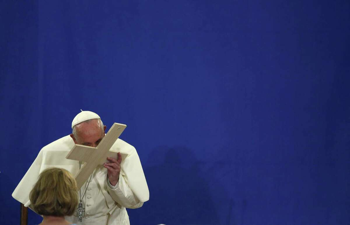 Pope Francis kisses a cross given to him by a woman at Our Lady Queen of Angels school in the Harlem neighborhood of New York, Friday, Sept. 25, 2015. (John Taggart/Pool Photo via AP)