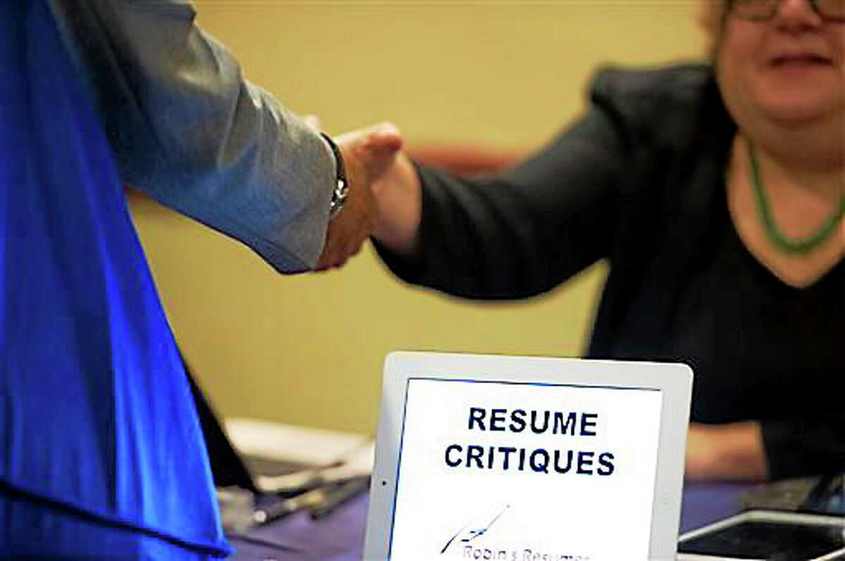 FILE - In this Thursday, May 30, 2013, photo, a job seeker stops at a table offering resume critiques during a job fair held in Atlanta. The Labor Department reports on the weekly jobless claims on Thursday, April 17, 2014.