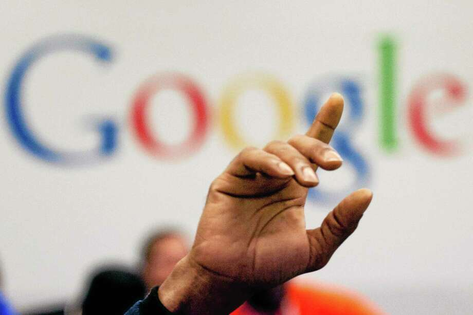 FILE - In this Oct. 17, 2012, file photo, a man raises his hand during at Google offices in New York. People should have some say over the results that pop up when they conduct a search of their own name online, Europe's highest court said Tuesday, May 13, 2014. (AP Photo/Mark Lennihan, File) Photo: AP / AP