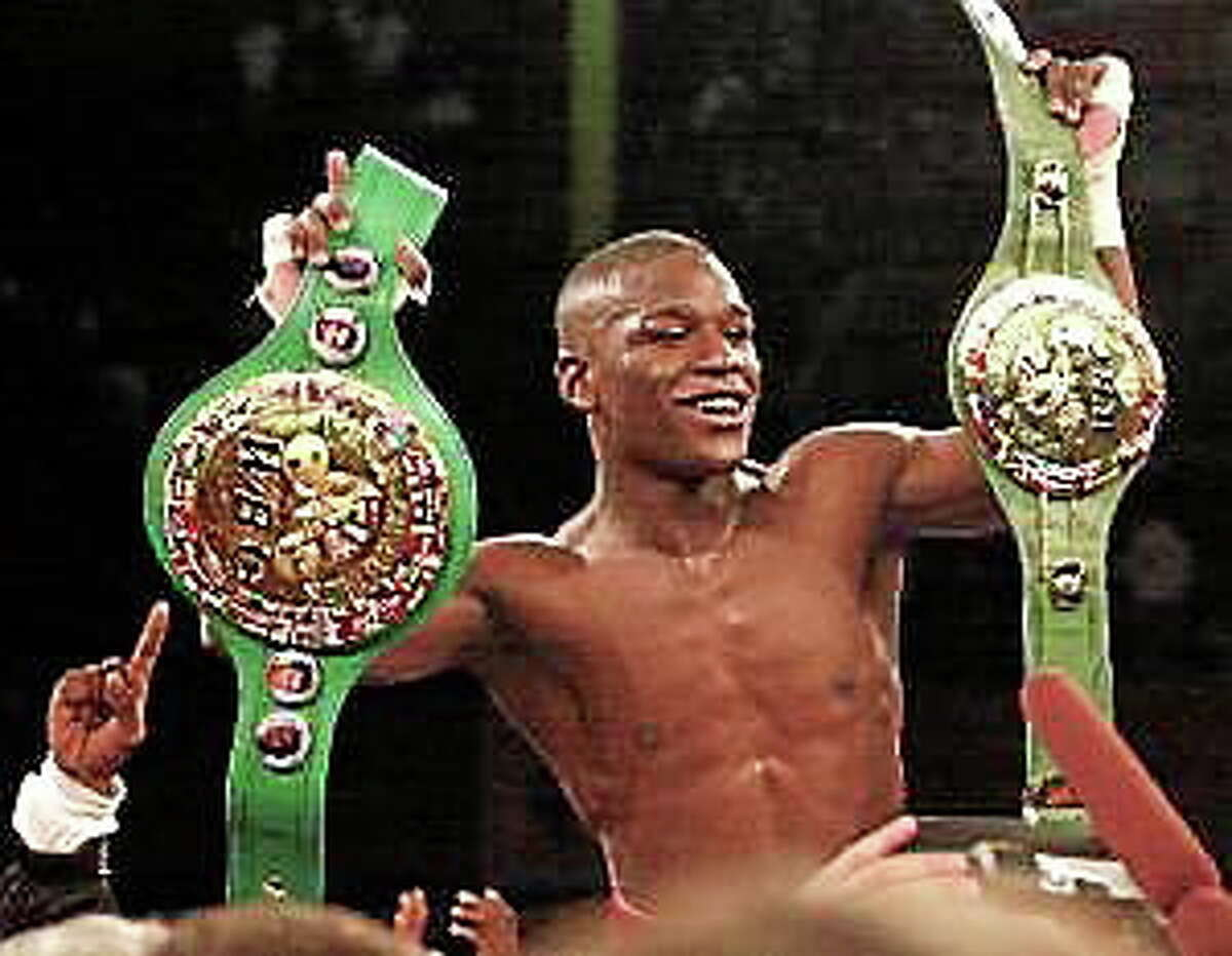 Floyd Mayweather Jr. holds championship belts after retaining his WBC super featherweight title with a win over Jesus Chavez on Nov. 10, 2001, in San Francisco.